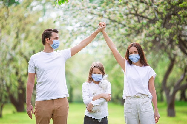 Rodzina nosząca ochronną maskę medyczną w celu zapobiegania wirusom na zewnątrz w parku