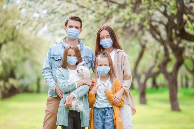 Rodzina nosząca ochronne maski medyczne w celu zapobiegania wirusom