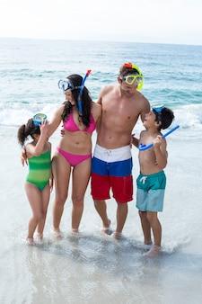 Rodzina noszenie okularów do nurkowania stojąc na brzegu morza