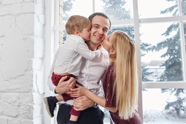 Rodzina obchodzi boże narodzenie i nowy rok. mama tata i syn przytulają się, rodzinne wakacje