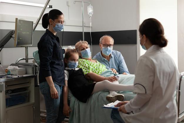Rodzina odwiedzająca pacjenta starszej starszej kobiety podczas noszenia ochronnej maski na twarz