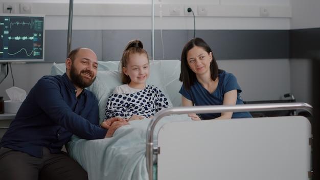 Rodzina ogląda film animowany w telewizji na oddziale szpitalnym w oczekiwaniu na zda...