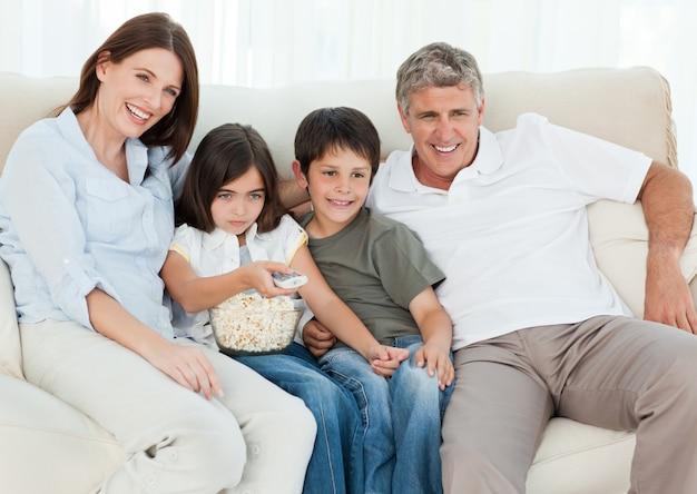 Rodzina ogląda tv podczas gdy jedzą popkorn