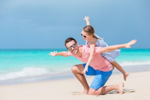 Rodzina ojciec i sporty mała dziewczynka ma zabawę na plaży