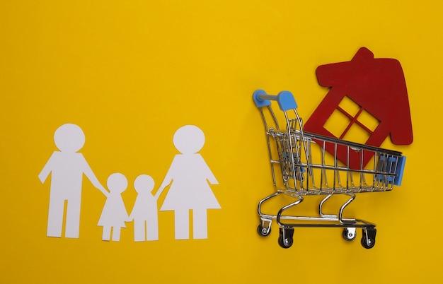 Rodzina papieru razem i wózek na zakupy z domem na żółto. koncepcja zakupu domu