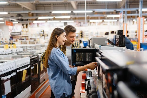 Rodzina para wybiera kuchenkę mikrofalową w sklepie elektronicznym. mężczyzna i kobieta kupują domowe urządzenia elektryczne na rynku