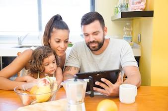 Rodzina patrząc na ekran cyfrowy tablet podczas śniadania