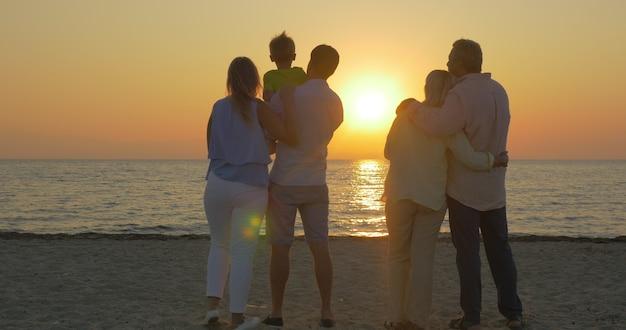 Rodzina patrząca na złoty zachód słońca nad morzem