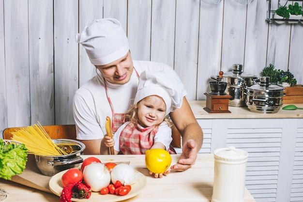 Rodzina, piękna córka tata w domu, w kuchni, śmiejąc się i przygotowując razem jedzenie