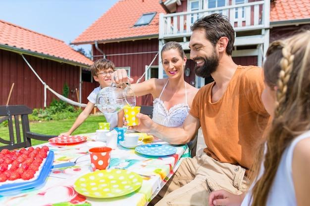 Rodzina pije kawę i je ciasto przed domem