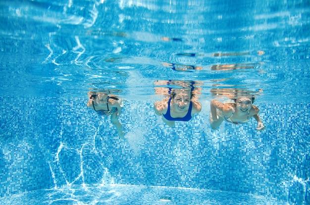 Rodzina pływa w basenie pod wodą, szczęśliwa aktywna matka i dzieci bawią się pod wodą, fitness i sport z dziećmi na wakacjach