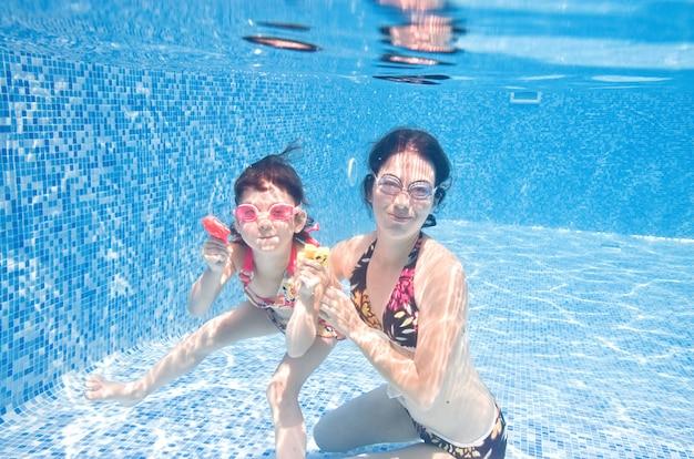 Rodzina pływa w basenie pod wodą, szczęśliwa aktywna matka i dziecko bawią się pod wodą, fitness i sport z dzieckiem na wakacjach w ośrodku