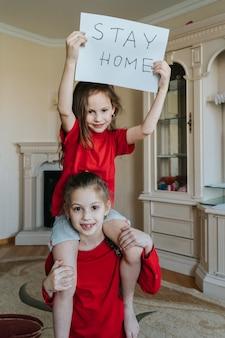 """Rodzina pobyt w domu koncepcja. dwie dziewczyny z napisem """"zostań w domu w celu ochrony przed wirusami i dbaj o swoje zdrowie z covid-19"""". koncepcja kwarantanny."""