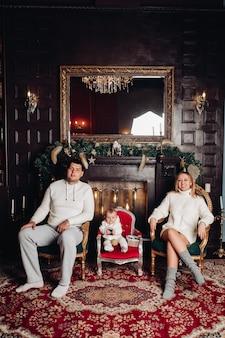 Rodzina pozowanie w urządzonym salonie. urocza kobieta, mężczyzna i dziecko ubrane w przytulne białe ubrania z dzianiny.