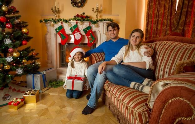 Rodzina pozuje w salonie ozdobionym na boże narodzenie z płonącym kominkiem