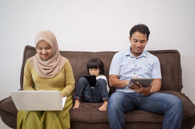 Rodzina pracująca zdalnie z domu siedząca razem