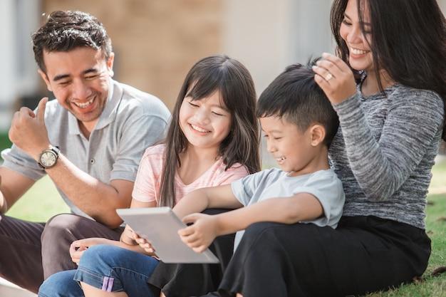 Rodzina przed domem za pomocą tabletu