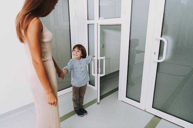 Rodzina przy klinice wejście kobieta przynosi małego syna