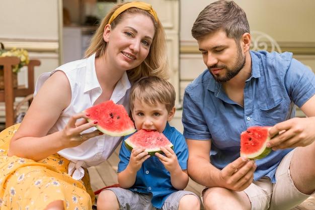 Rodzina razem jedząca arbuza obok przyczepy kempingowej