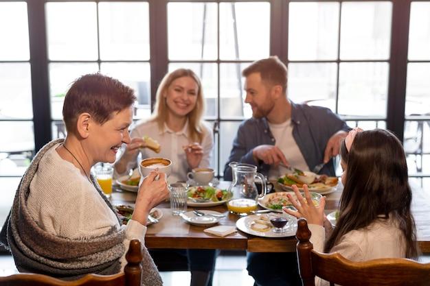Rodzina razem jeść przy stole średnie ujęcie