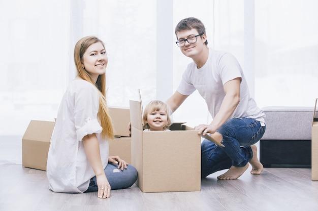 Rodzina razem szczęśliwa młoda piękna z małym dzieckiem przenosi się z pudełkami do nowego domu
