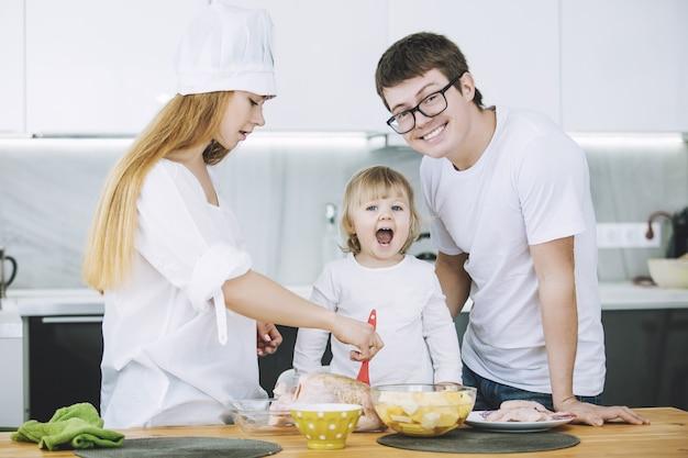 Rodzina Razem Szczęśliwy Młody Piękny Z Małym Dzieckiem Przygotowując Obiad W Kuchni W Domu Premium Zdjęcia