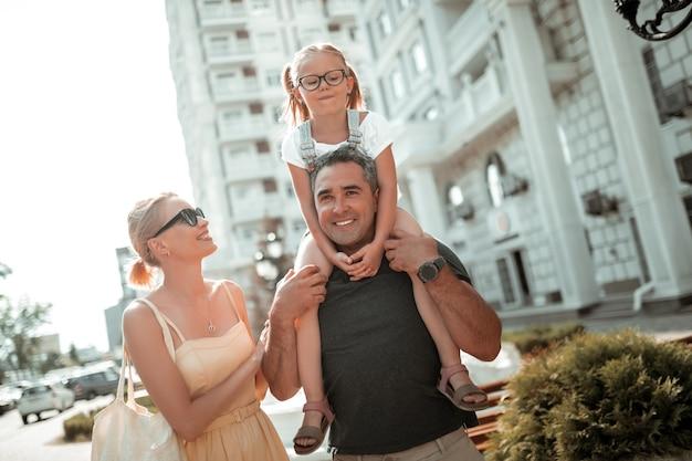 Rodzina razem. uśmiechnięta dziewczynka siedzi na ramionach swojego ojca idącego obok swojej wesołej matki.