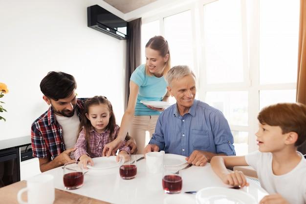 Rodzina razem w domu pije tee.
