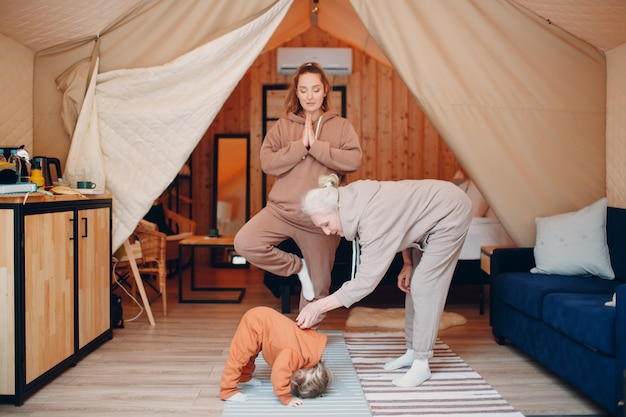 Rodzina robi ćwiczenia sportowe idoors. młoda i starsza starsza kobieta relaksuje w namiocie kempingowym glamping. matka i córka nowoczesne w koncepcji stylu życia wakacje fitness.
