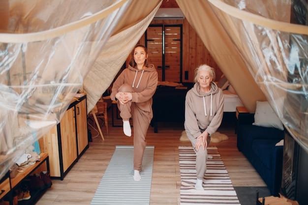 Rodzina robi ćwiczenia sportowe w pomieszczeniu. młoda i starsza starsza kobieta relaksuje w namiocie kempingowym glamping. matka i córka nowoczesne w koncepcji stylu życia wakacje fitness.