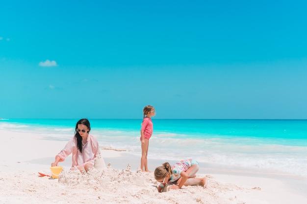 Rodzina robi piaska kasztelowi przy tropikalną biel plażą. matka i dwie dziewczyny bawiące się piaskiem na tropikalnej plaży