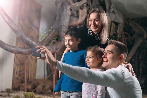Rodzina robi sobie selfie przed szkieletem mamuta w muzeum paleontologii.