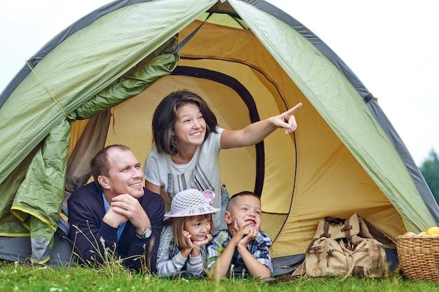 Rodzina rodzice i dwoje dzieci w namiocie obozowym. szczęśliwa matka, ojciec, syn i córka na letnie wakacje. mama pokazuje coś w oddali