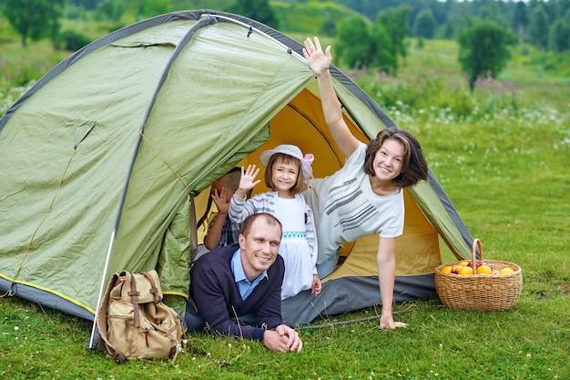 Rodzina rodzice i dwoje dzieci w namiocie obozowym. szczęśliwa matka, ojciec, syn i córka na letnie wakacje.