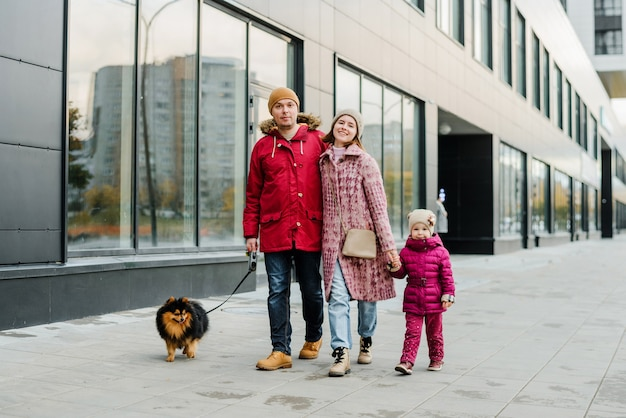 Rodzina, rodzicielstwo i ludzie koncepcja szczęśliwej matki, ojca i dziewczynki spaceru w mieście jesienią i zabawy.