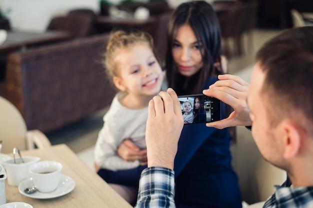Rodzina, rodzicielstwo, technologia, koncepcja ludzi. szczęśliwy ojciec biorąc zdjęcie swojej małej córki i żony smartfonem, obiad w restauracji
