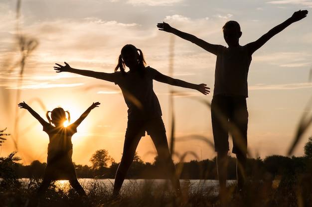 Rodzina rodziców i dzieci sylwetki o zachodzie słońca na zewnątrz