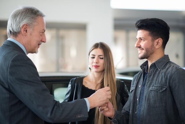 Rodzina rozmawia ze sprzedawcą i wybiera nowy samochód w salonie