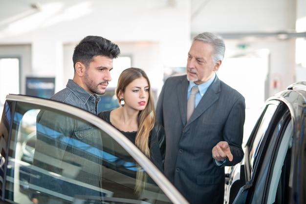 Rodzina rozmawia ze sprzedawcą i wybiera nowy samochód w salonie.