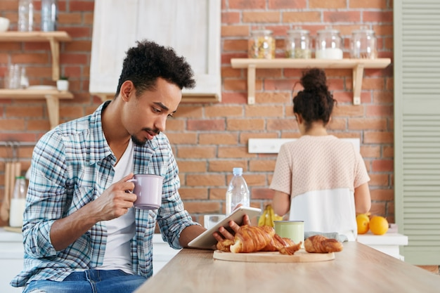 Rodzina rutynowych koncepcji. samiec rasy mieszanej uważnie czyta wiadomości na tablecie, siedzi w kuchni,