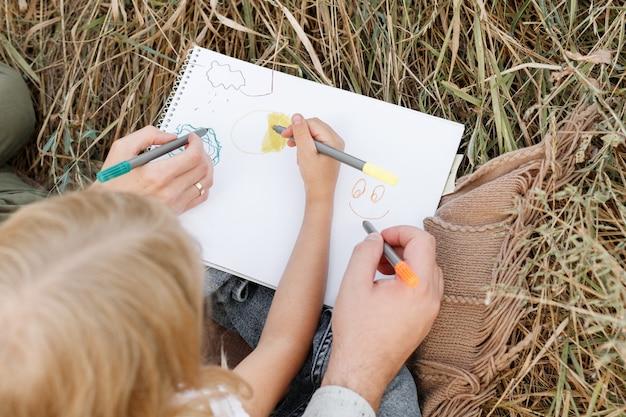Rodzina rysuje w albumie markerami. zbliżenie