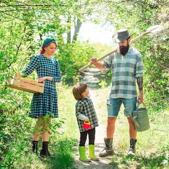 Rodzina sadząca ojciec matka i mali chłopcy bawią się na farmie na wiosnę