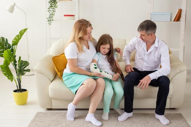 Rodzina siedząca na kanapie w salonie córka ma kontuzjowaną rękę, ale jest szczęśliwa, że możemy być razem