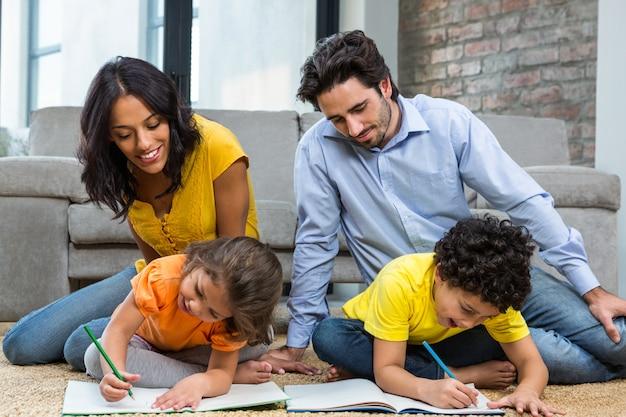 Rodzina siedzi na dywanie w salonie