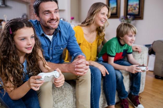 Rodzina siedzi na kanapie i gra w gry wideo
