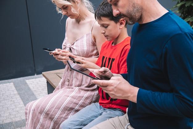 Rodzina siedzi na ławce w letni dzień w jednym mieście. wszyscy patrzą na smartfon lub tablet. nie zwracają na siebie uwagi. zdjęcie wysokiej jakości