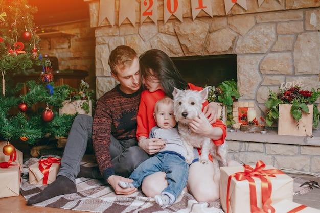 Rodzina siedzi na podłodze z brązowych prezentów i choinki