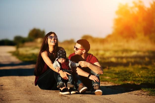 Rodzina siedzi na polnej drodze z dzieckiem