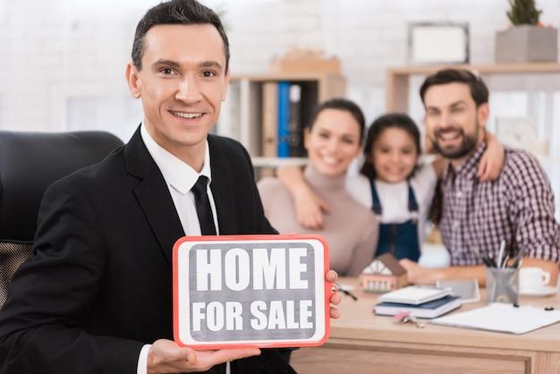 Rodzina siedzi, podczas gdy agent nieruchomości, który posiada znak z napisem.