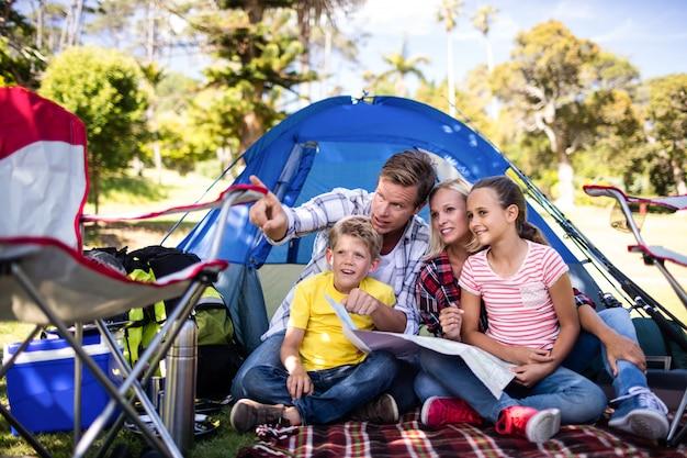 Rodzina siedzi przed namiotem